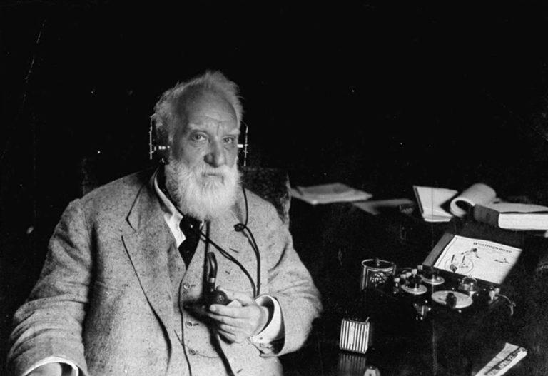 Alexander Graham Bell con los audífonos del teléfono.