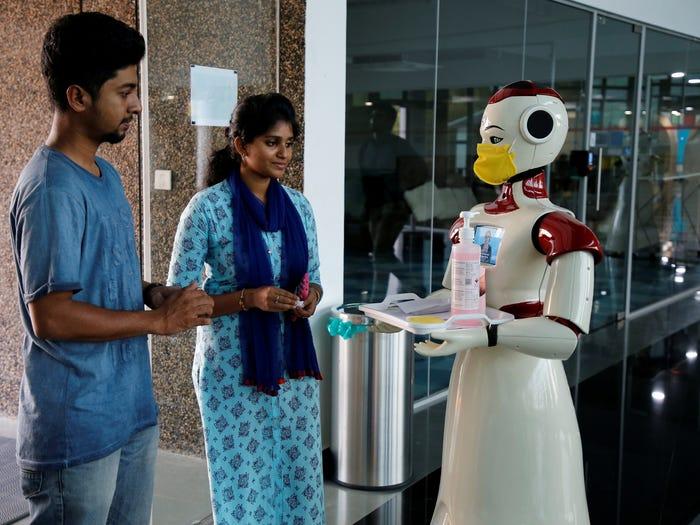 Robots en la India reparten cubrebocas y sanitizante para alertar sobre el Coronavirus.